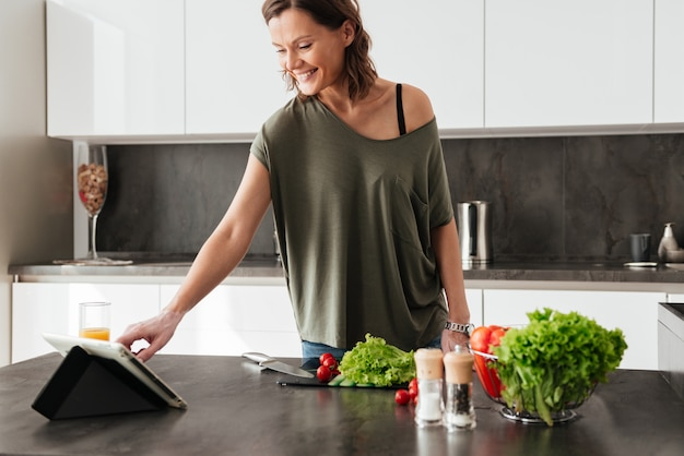 Sonriente mujer casual de pie cerca de la mesa con verduras en la cocina y usando la computadora tablt