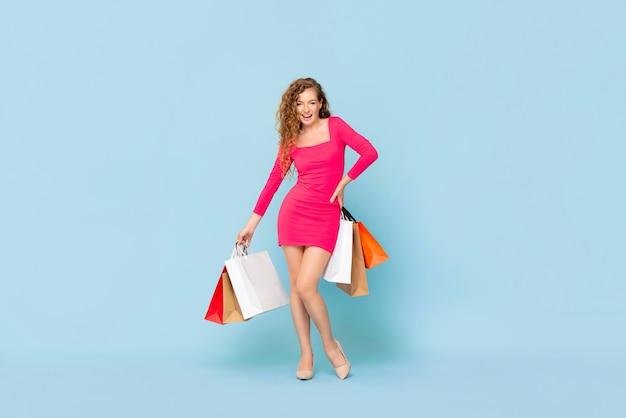 Sonriente mujer caucásica con coloridos bolsos de compras de pie en la pared aislada azul claro