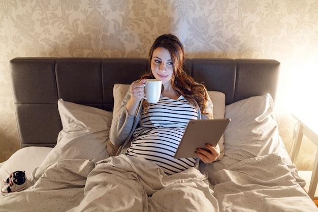 Sonriente mujer caucásica embarazada linda con cabello largo castaño acostado en la cama, bebiendo té y leyendo sobre bebés en tableta. hora de la tarde.