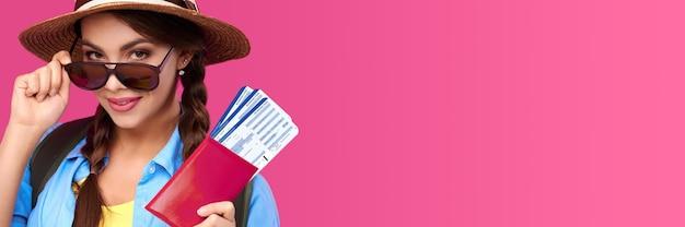Sonriente mujer caucásica con gafas de sol con pasaporte con boleto de viaje en el interior sobre fondo rosa aislado. tiro de studoi
