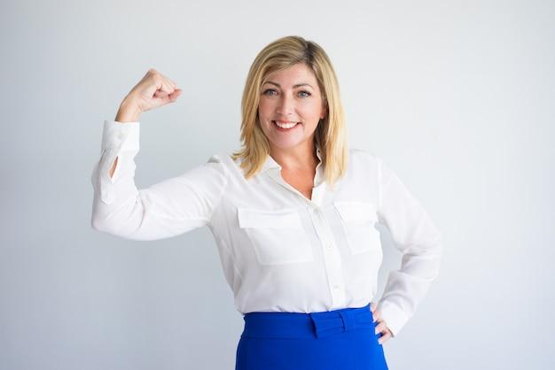 Sonriente mujer caucásica madura en blusa formal flexionando bíceps.
