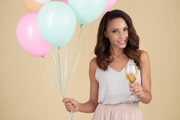 Sonriente mujer caucásica posando en estudio con globos y copa de vino
