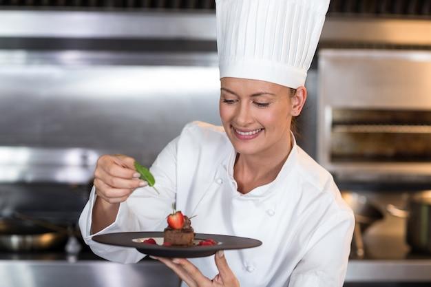 Sonriente mujer chef con plato de comida en la cocina