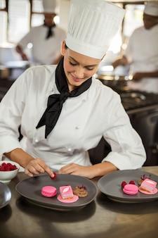 Sonriente mujer chef terminando platos de postre