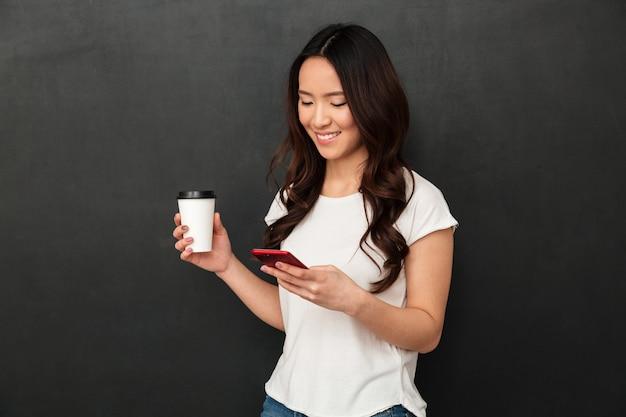 Sonriente mujer china escribiendo mensajes de texto o desplazarse por la red social en el teléfono inteligente mientras bebe café para llevar, aislado sobre la pared gris