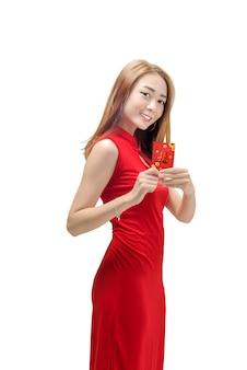 Sonriente mujer china con vestido tradicional mostrando angpao