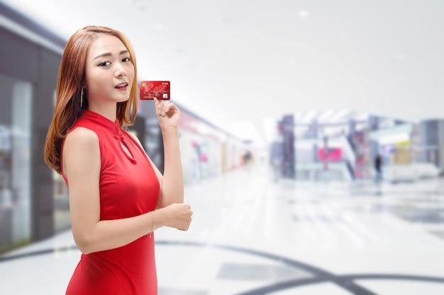 Sonriente mujer china con vestido tradicional con tarjeta de crédito