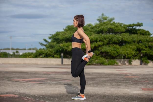 Sonriente mujer corredor asiático haciendo ejercicio de estiramiento, preparándose para el entrenamiento matutino y el concepto de estilo de vida en la ciudad