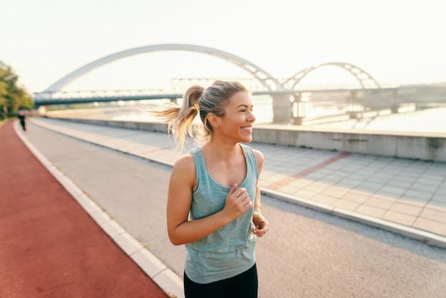 Sonriente mujer corredor con cabello rubio y cola de caballo vestida con ropa deportiva corriendo en el kay temprano en la mañana en verano.