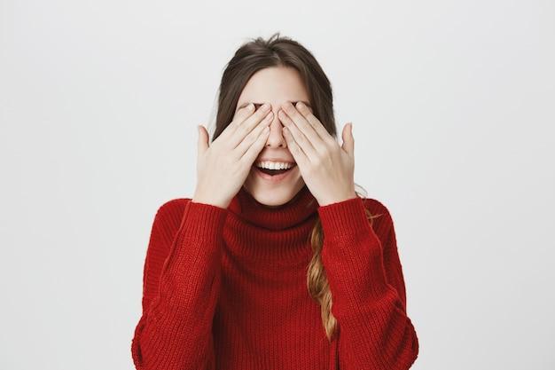 Sonriente mujer cubre los ojos, espera sorpresa