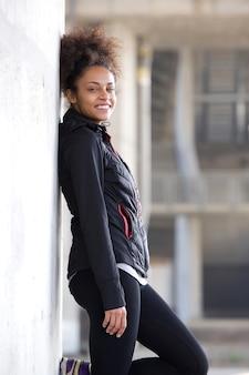 Sonriente mujer de deportes relajante apoyado contra la pared