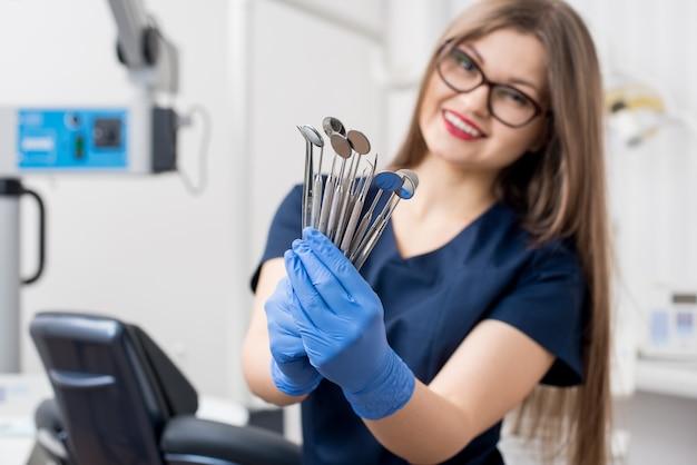 Sonriente mujer dentista con guantes azules con herramientas - espejos dentales y sondas dentales en el consultorio dental