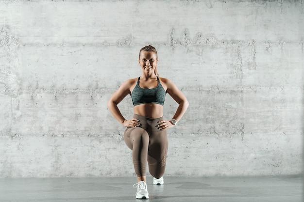Sonriente mujer deportiva caucásica vestida con ropa deportiva y con cola de caballo haciendo estocadas en el gimnasio.