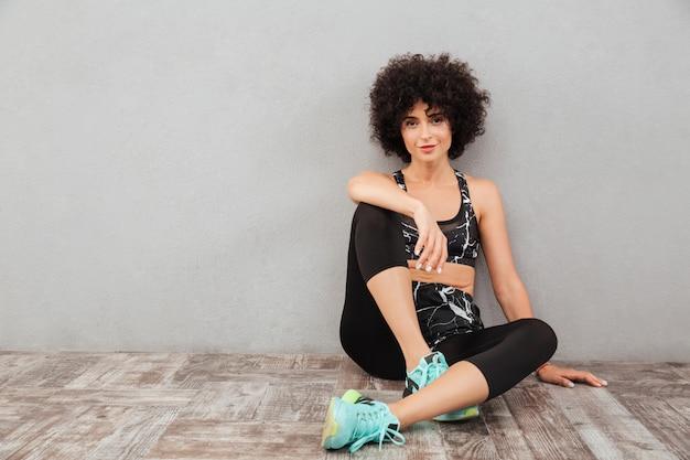 Sonriente mujer deportiva rizada sentada en el suelo