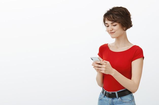Sonriente mujer elegante usando teléfono móvil, enviando mensajes de texto o navegando por las redes sociales