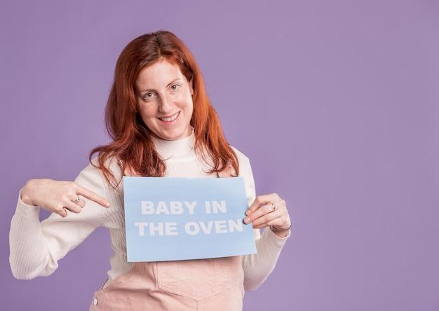 Sonriente mujer embarazada apuntando al bebé en el mensaje del horno
