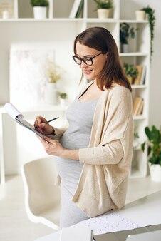 Sonriente mujer embarazada atractiva en cardigan y anteojos de pie en el escritorio y tomando notas en papeles mientras lo analiza en la oficina en casa