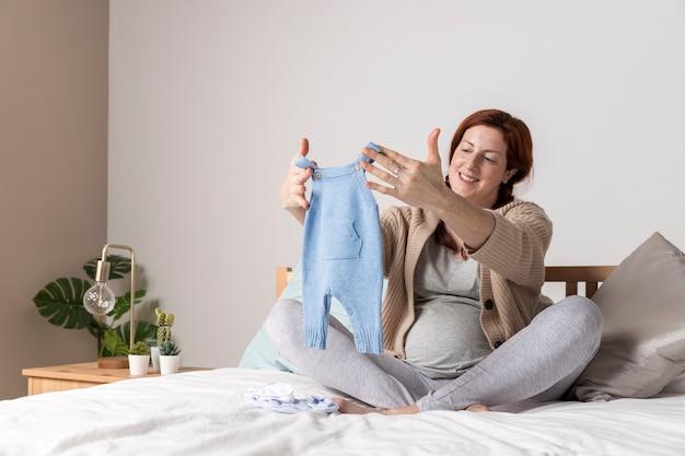 Sonriente mujer embarazada mirando ropa de bebé