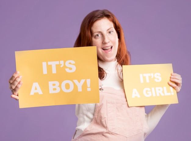 Sonriente mujer embarazada sosteniendo papel con género de bebé