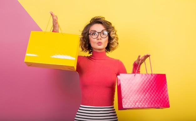 Sonriente mujer emocionada atractiva en elegante traje colorido con bolsas de la compra.