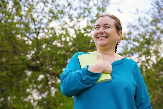 Sonriente mujer emocionada impresionada con la historia del libro