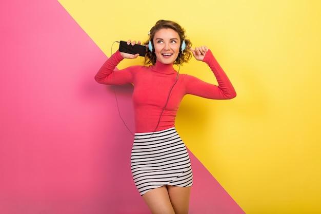 Sonriente mujer emocionada sonriente atractiva en elegante traje colorido bailando y escuchando música en auriculares sobre fondo amarillo rosa, tendencia de moda de verano