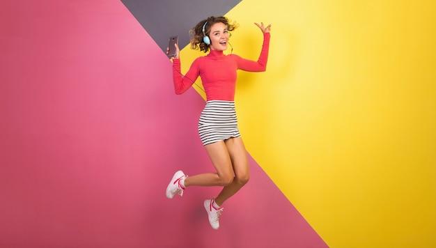 Sonriente mujer emocionada sonriente atractiva en elegante traje colorido saltando y escuchando música en auriculares sobre fondo amarillo rosa, tendencia de moda de verano