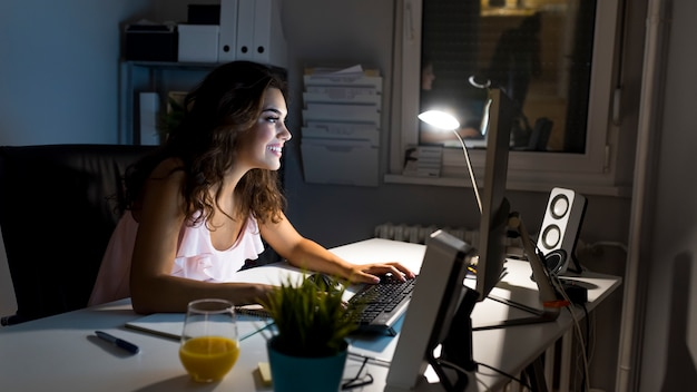 Sonriente mujer empresaria trabajando desde su casa hasta altas horas de la noche