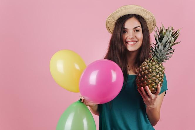 Sonriente mujer en un sombrero posa con globos de colores y una piña
