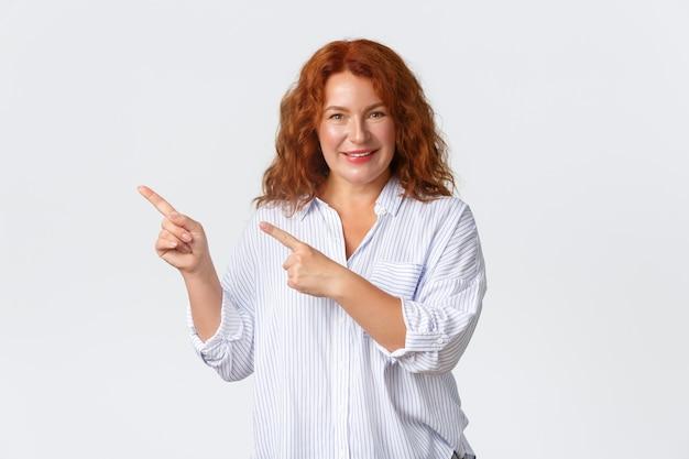 Sonriente mujer encantadora pelirroja de mediana edad que muestra el anuncio, señalando con el dedo la esquina superior izquierda. señora alegre con banner de producto de demostración de cabello jengibre sobre fondo blanco.