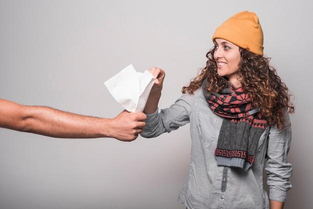 Sonriente mujer enferma tomando papel de seda de la mano del hombre