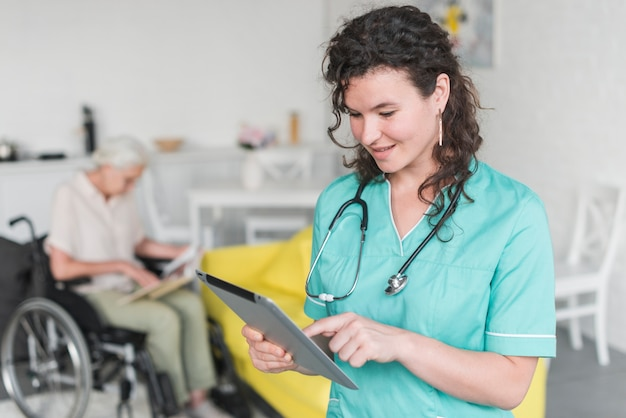 Sonriente mujer enfermera conmovedora tableta digital