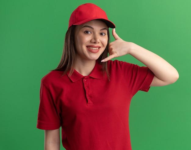 Sonriente mujer de entrega bonita en gestos uniformes me llaman signo aislado en la pared verde con espacio de copia