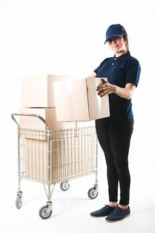 Sonriente mujer de entrega que lleva la caja del paquete delante de fondo blanco