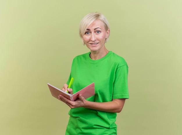 Sonriente mujer eslava rubia de mediana edad mirando al frente sosteniendo bolígrafo y bloc de notas mirando a la cámara aislada en la pared verde oliva con espacio de copia