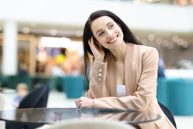 Sonriente mujer feliz está sentada en la cafetería