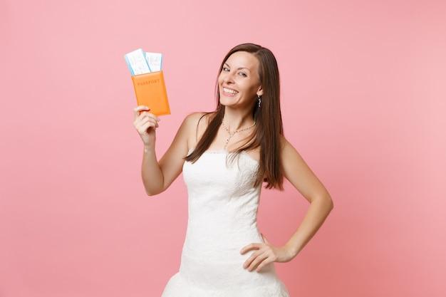 Sonriente mujer feliz en vestido blanco con pasaporte y boleto de embarque, ir al extranjero, vacaciones