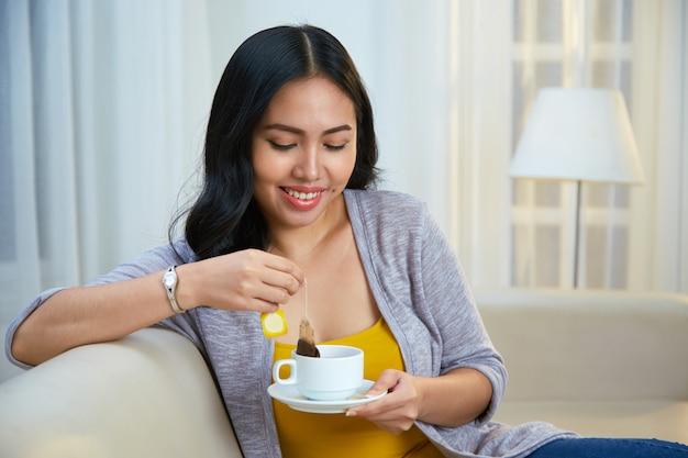 Sonriente mujer filipina elaborando té en el sofá