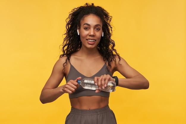Sonriente mujer de fitness bastante joven escuchando música con auriculares inalámbricos y abriendo una botella de agua aislada sobre la pared amarilla