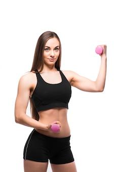 Sonriente mujer fitness ejercicio con mancuernas aislado sobre fondo blanco.