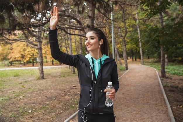 Sonriente mujer fitness escuchando música con auriculares, sosteniendo una botella de agua mientras está de pie en el parque