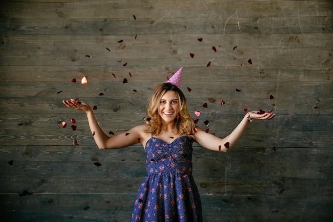 Sonriente mujer hermosa celebrando unas vacaciones, jugando con confeti