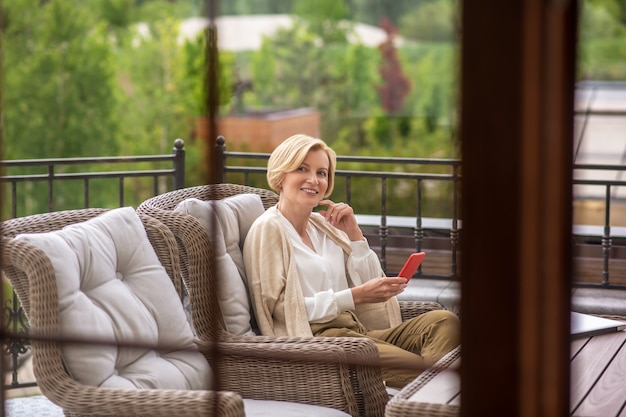 Sonriente mujer hermosa contenta con un teléfono celular en la mano sentado en el sillón en una mesa de madera