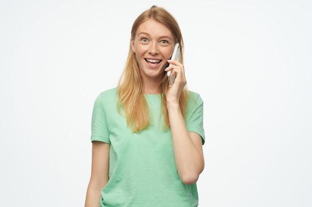Sonriente mujer hermosa con pecas en menta se ve feliz y hablando por teléfono móvil en blanco