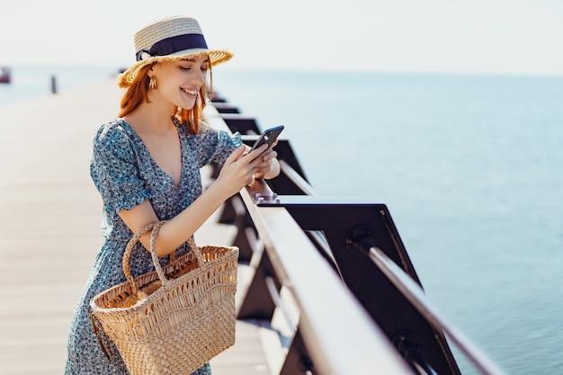 Sonriente mujer hermosa permanecer en el muelle y navegar por teléfono inteligente en un día soleado con ropa de moda ...