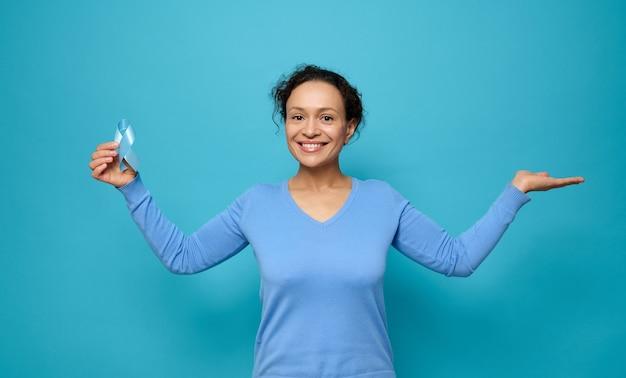 Sonriente mujer hermosa de raza mixta con ropa casual azul, sostiene una cinta de conciencia azul y pone la palma hacia arriba sosteniendo un espacio de copia imaginaria para publicidad médica para el día mundial de la diabetes, 14 de noviembre