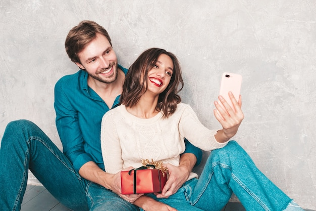 Sonriente mujer hermosa y su guapo novio. familia alegre feliz posando junto a la pared gris. día de san valentín. modelos abrazándose y dándole una caja de regalo a su novia.