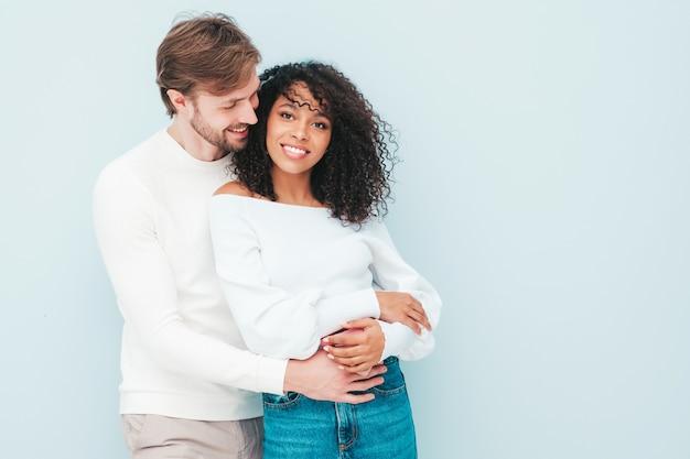 Sonriente mujer hermosa y su guapo novio. familia multirracial alegre feliz que tiene momentos tiernos en gris