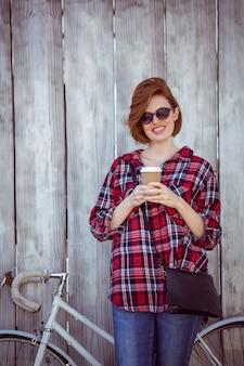 Sonriente mujer hipster con café y una bicicleta, de pie