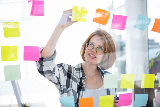 Sonriente mujer hipster pegar notas en un tablón de anuncios en la oficina